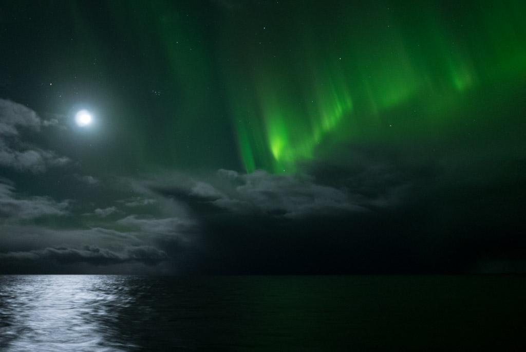 Mond, Plejaden und Polarlicht über Wolken